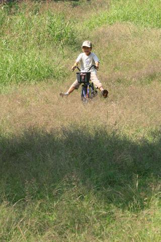 自転車で草原の坂を下る恒太